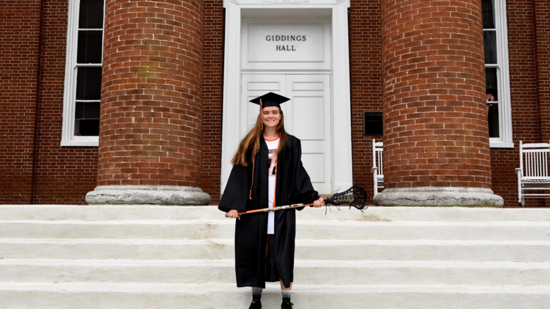 Avery Blackmon in cap and gown on steps of Giddings